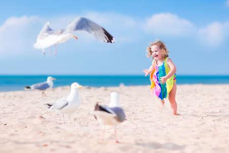 dieren: Grappig lauging peuter, schattig meisje met krullend haar in een kleurrijke jurk spelen met zeemeeuw vogels, rennen en springen op een prachtig strand op een zonnige warme zomerdag