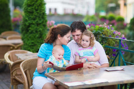 Happy family of four, young parents and their two kids, adorable toddler girl and cute baby boy enjoying lunch at a beautiful outside cafe in a small traditional German town