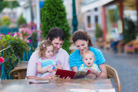 Happy family of four, young parents and their two kids, adorable toddler girl and cute baby boy enjoying lunch at a beautiful outside cafe in a small traditional German town photo
