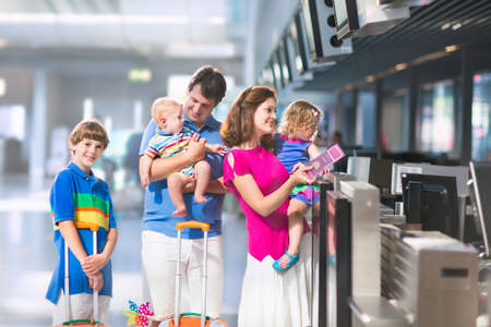 Big happy family with three kids travelling by airplane at Dusseldorf International airport, parents with teenager boy, toddler girl and little baby holding colorful luggage for summer beach vacation