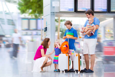 airport check in counter: Big happy family with three kids travelling by airplane at Dusseldorf International airport, parents with teenager boy, toddler girl and little baby holding colorful luggage for summer beach vacation