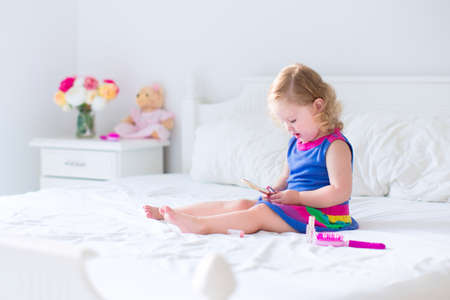 child in bed: Cute little child, beautiful toddler girl with curly hair applying make up holding lipstick and mirror sitting on a white bed in a sunny bedroom playing with her toy teddy bear