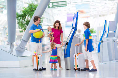 check in: Big happy family with three kids travelling by airplane at Dusseldorf International airport, parents with teenager boy, toddler girl and little baby holding colorful luggage for summer beach vacation
