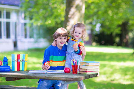 Two laughing kids happy being back to school, sitting outside a green sunny school yard reading books and enjoying healthy snack for lunch, sandwich and fruit, apple  photo