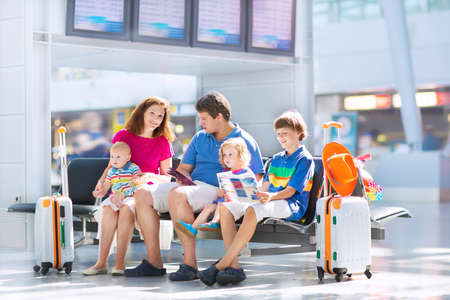 airport window: Big happy family with three kids travelling by airplane at Dusseldorf International airport, young parents with teenager boy, toddler girl and little baby holding colorful luggage for summer beach vacation Stock Photo