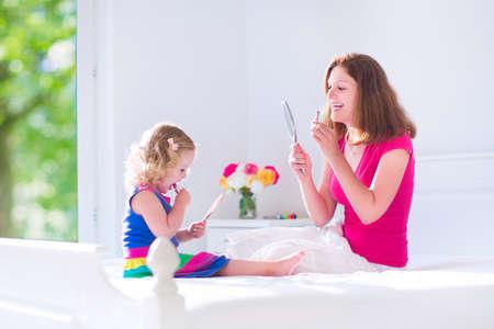 hacer el amor: Feliz hermosa joven madre y su hija adorable, niña linda con el pelo rizado de aplicar maquillaje, lápiz de labios, mirando en los espejos de mano, sentado en una cama blanca en una habitación soleada con ventana Foto de archivo