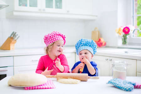 cute guy: Cute kids, adorable little girl and funny baby boy wearing pink and blue chef hats playing with baking a pie in a sunny white kitchen