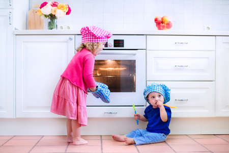 baking oven: Cute kids, adorable little girl and funny baby boy wearing pink and blue chef hats playing with baking a pie in a sunny white kitchen