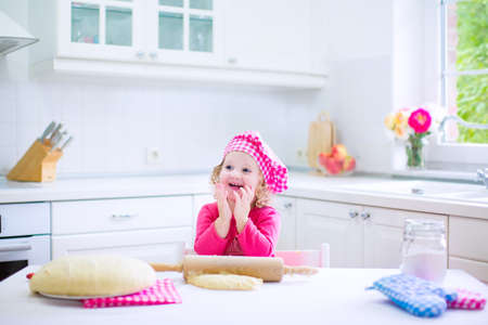 pink hat: Adorable little child, funny curly toddler girl in a pink chef hat baking a pie rolling sitting in a white sunny kitchen with big window