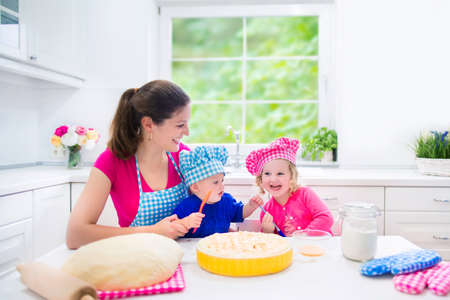 home baking: Young happy mother and her kids, adorable toddler girl and a little funny baby boy wearing pink and blue chef hats baking a pie together in a white sunny kitchen with big window