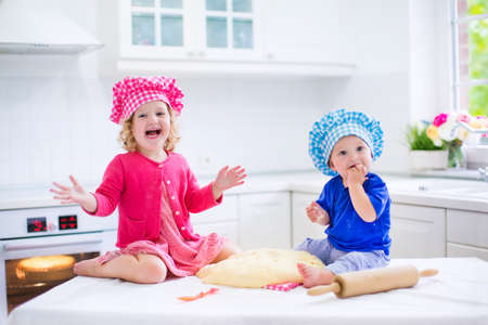kitchen device: Cute kids, adorable little girl and funny baby boy wearing pink and blue chef hats playing with baking a pie in a sunny white kitchen