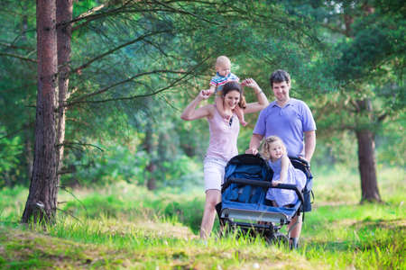 all in: Active family, young parents and their two little children, adorable toddler girl and a cute funny baby boy, hiking together in a pine forest pushing an all terrain twin stroller