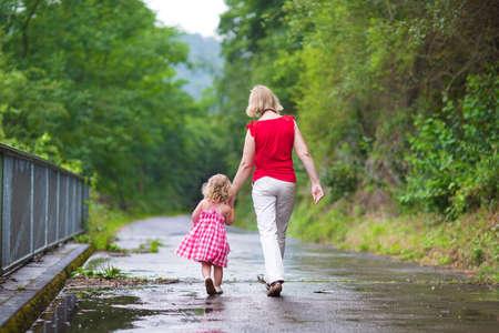 niños caminando: Madre y niña niño rizado caminar juntos en un parque en un día de verano húmedo después de la lluvia, vista desde la parte de atrás