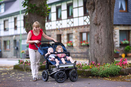 Young beautiful woman with a double jogging stroller with two kids, baby boy and little toddler girl, brother and sister, walking in a beautiful German village with traditional old houses