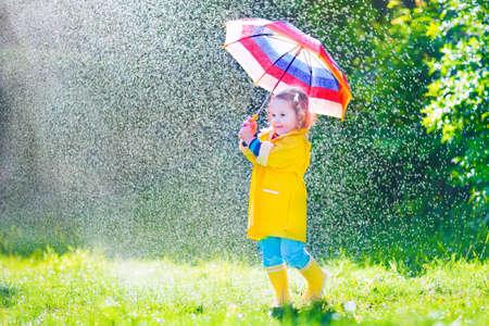botas de lluvia: Chica rizada linda divertida del niño que desgasta la capa impermeable amarillo y botas de la celebración de paraguas de colores jugando en el jardín por la lluvia y el sol el tiempo en un otoño caliente o sumemr días