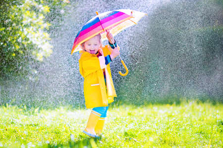 Funny cute curly toddler girl wearing yellow waterproof coat and boots holding colorful umbrella playing in the garden by rain and sun weather on a warm autumn or sumemr day Stockfoto