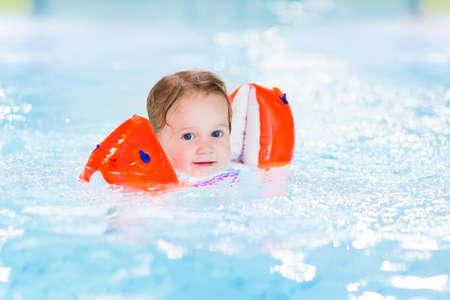 Happy toddler girl having fun in a swimming pool photo
