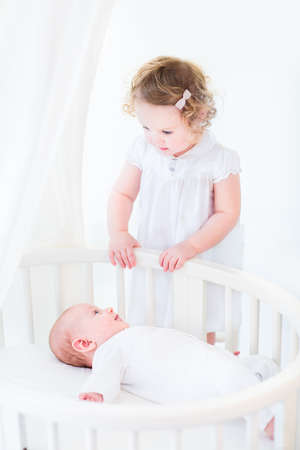 Adorable siblings, newborn baby boy and a toddler girl playing in a white sunny bedroom with a round crib photo