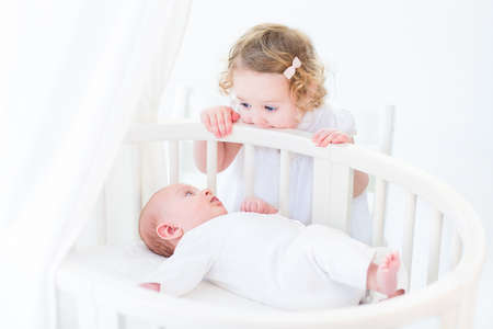 bassinet: Cute newborn baby boy watching his toddler sister standing at his white round crib in a sunny bedroom