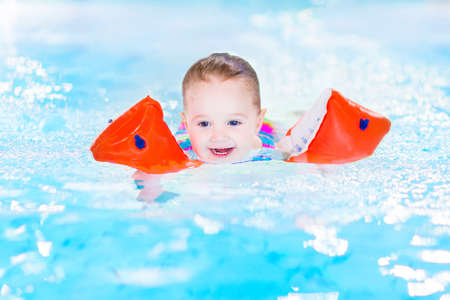 swimming pool float: Happy laughing toddler girl having fun in a swimming pool