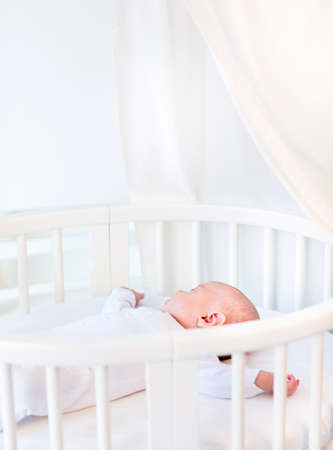 sleeping rooms: Portrait of a newborn baby boy sleeping in a white round crib with canopy