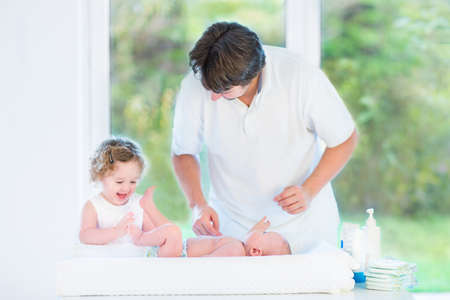 diaper changing table: Cute newborn baby looking at his father and toddler sister changing his diaper in a room with a big window