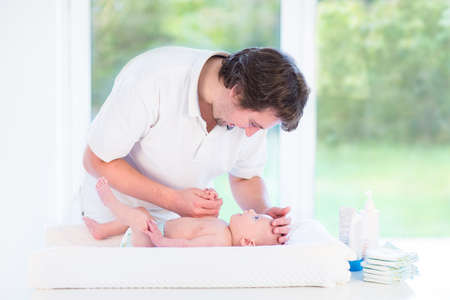 diaper changing table: Young loving father looking at his little baby son changing a diaper in a white room with a big window with garden view   Stock Photo