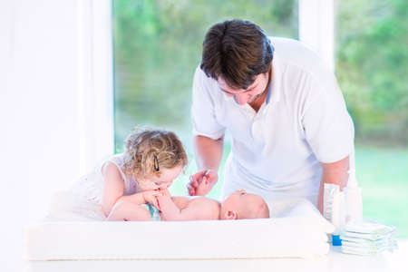 Cute toddler girl kissing her newborn baby brother on a white changing table next to a big window   photo