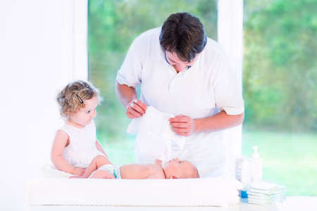 Young father dressing his newborn baby son and his toddler daughter helping him in a white room with a big garden view window   photo