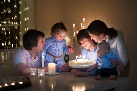 Young happy family with three kids celebration the birthday of their son blowing out the candles on a cake in a dark living room