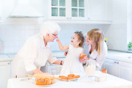 great grandmother: Funny toddler girl playing in a kitchen, having fun baking an apple pie with her grandmothers