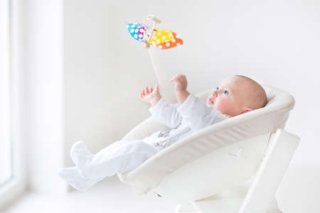 baby chair: Cute newborn baby boy watching a colorful mobile toy sitting in a white high chair next to a window   Stock Photo