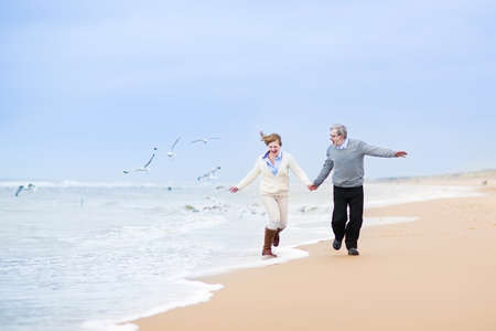 aged: Happy mature couple running at a beautiful winter beach with seagulls