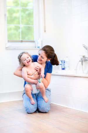 Jonge moeder en haar gelukkige baby spelen samen in een witte zonnige bad kamer met een raam uitzicht op de tuin