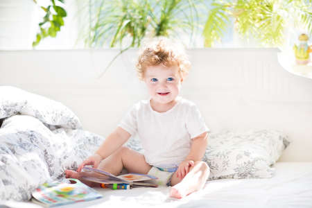 Happy funny baby reading a book in her parents bed on a sunny morning in a beautiful white bedroom with a window