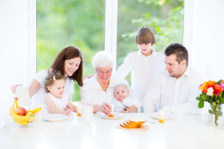 Happy young family with three children - teenager boy, cute toddler girl and a newborn baby - enjoying breakfast in a white sunny dining room with a big garden view window   photo