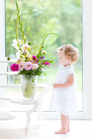 Beautiful Toddler Girl Watching Flowers In A Big Vase Next To