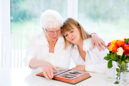 familias unidas: Hermosa mujer y su amorosa madre viendo un álbum de foto blanco y negro en una soleada sala de estar blanca Foto de archivo