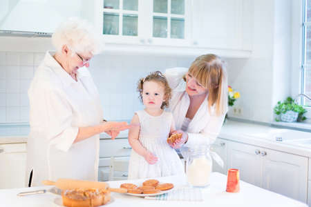 Funny toddler girl baking an apple pie with her grandmothers in a sunny white kitchen   photo