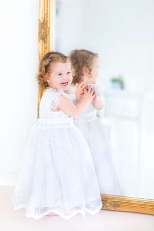 Beautiful toddler girl in a white dress standing next to a big mirror   photo
