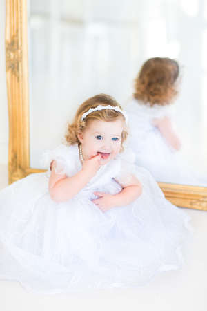 christening: Beautiful curly toddler girl in a white dress sitting next to a big mirror