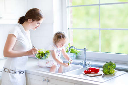 若い母と娘一緒に大きな庭と美しい白いキッチンでサラダを調理愛らしい幼児がウィンドウを表示します。 写真素材