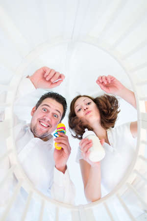 Happy young parents making funny faces looking at their baby in a white round crib - from baby perspective view   Stock Photo