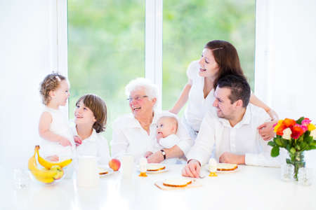 breakfast garden: Happy grandmother enjoying breakfast with her daughter and grandchildren - teenage boy, funny curly toddler girl with and newborn baby - sitting in a white dining room with a big garden view window