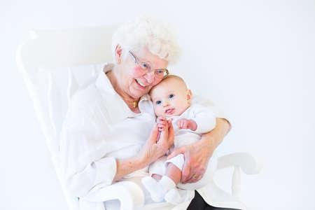 아름 다운 할머니는 흰색 흔들 의자에 앉아 그녀의 신생아 아기 손자 노래 스톡 콘텐츠 - 30780613