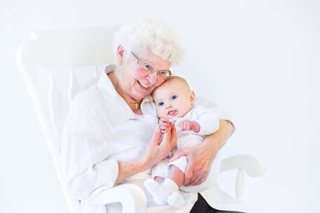 Beautiful grandmother singing to her newborn baby grandson sitting in a white rocking chair   Archivio Fotografico