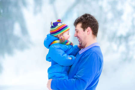 Young father playing with his funny baby in a snowy park   photo