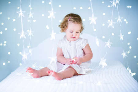 baby crib: Adorable toddler girl playing with Christmas lights sitting on a white bed