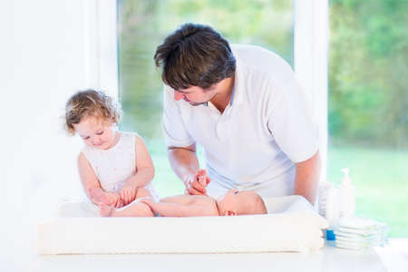 Adorable toddler girl helping her father to change a diaper of her newborn baby brother in a white room with a big garden view window on a sunny morning   Stock Photo