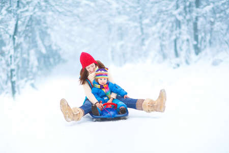 Young happy mother and her little toddler daughter enjoying a sledge ride in a beautiful snowy winter park